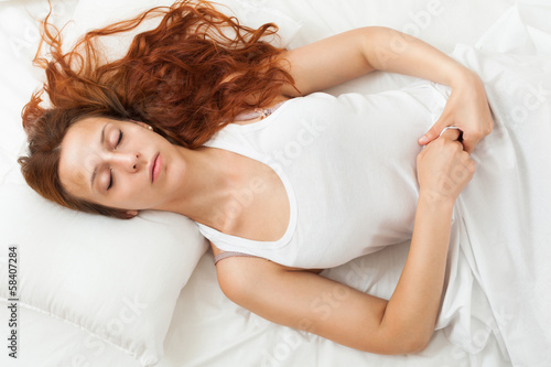 beauty bed-haired girl sleeping on white pillow in bed