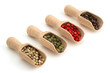 varieties of peppercorns in wooden scoops on white background