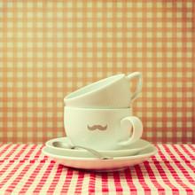 Kaffeetassen mit Hipster-Schnurrbart auf kariertem Tischtuch