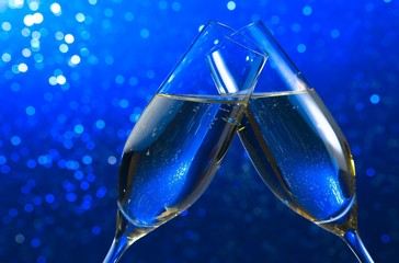 pair of a champagne flutes on blue light bokeh background