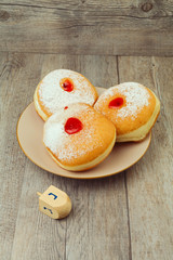 Donut for jewish holiday hanukkah on plate and dreidel