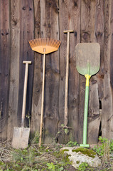 farmer gardener tools near  wooden barn wall