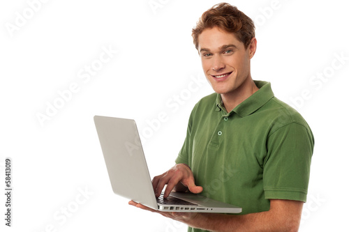 Handsome guy operating laptop