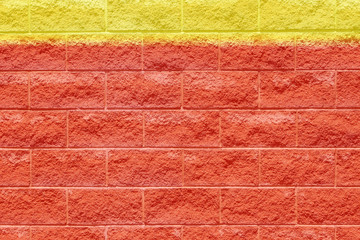 Red brick wall with yellow strip of painted color along top