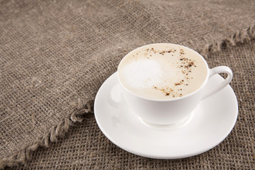White cup of cappuchino on burlap