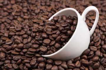 White cup with coffee beans close up