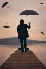 Man looks at sunset sky full of umbrellas