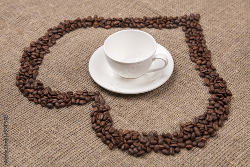 White cup of on burlap with coffee heart