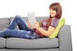 Young female with tablet computer or electronic book on sofa
