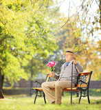Senior gentleman with bunch of flowers sitting on a bench