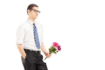 Worried young man with tie holding a bouquet of flowers