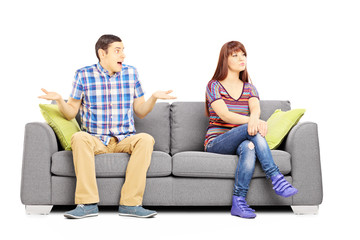 Young couple sitting on a couch during an argument