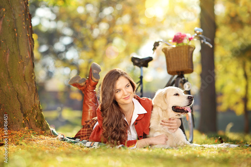 Young beautiful female on grass with her dog in a park