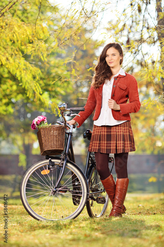 Young female with bicycle posing in park