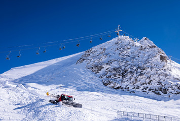 Chair lift and snow groomer in Alps