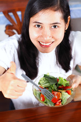 Smiling asian woman enjoying a fresh healthy salad