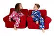 two children laughing wearing winter pajamas sitting in red chai