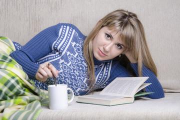 девушка читает книгу с кружкой чая, на диване