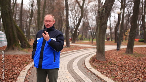 Adult man talking on  mobile in   autumn park