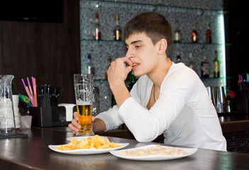 Young man sitting drinking and eating at a pub