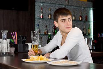 Young man sitting at a bar counter waiting