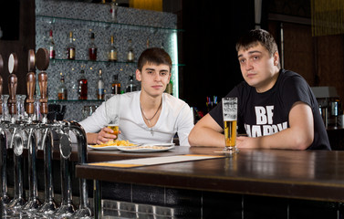Two teenage men drinking at the pub