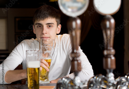 Young man drinking alone