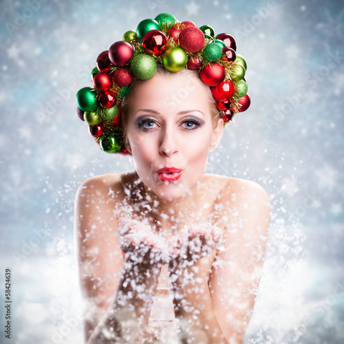 junge Frau pustet Schnee