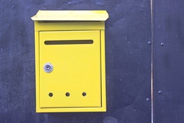 Yellow mailboxes on blue metal background