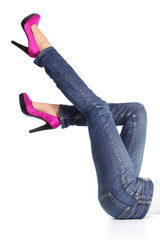 Woman legs with jeans and fuchsia high heels pointing up