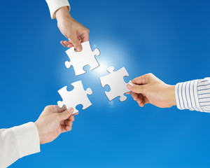 Hands hold puzzles with clear blue sky and sun light