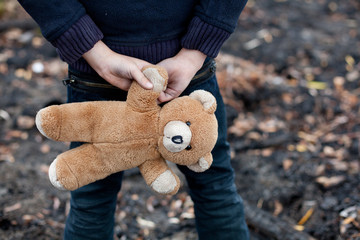 homeless boy holds in hands bear