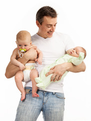 Smiling young man with two baby boys over white