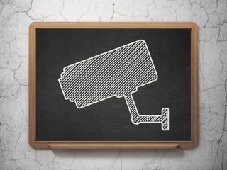 Protection concept: Cctv Camera on chalkboard background