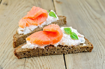 Sandwiches on bread with salmon and basil on board