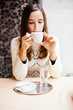 Young woman drinking coffee in cafe