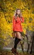 Beautiful elegant woman with orange coat posing in park
