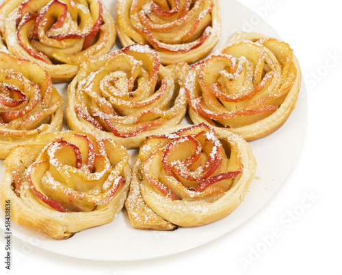 Sweet rolls with apples in the form of roses on plate on white b