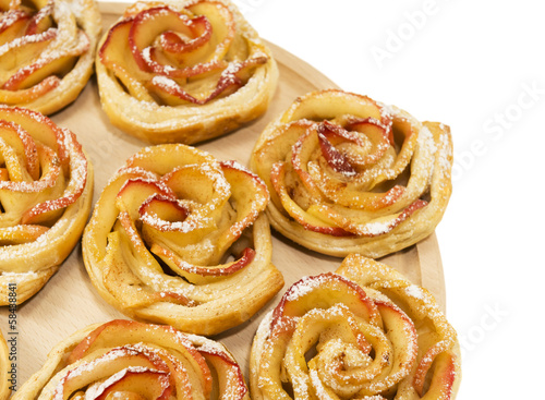 Sweet rolls with apples in the form of roses on wooden board on