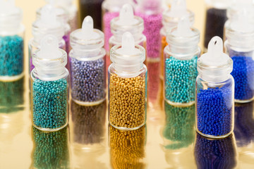 Small Glass Jars filled with Balls of Bead