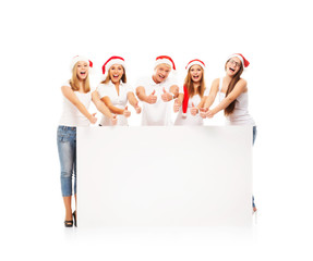 A group of happy teenagers in Christmas hats near a blank banner