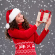 Smiling woman in santa hat with gift box