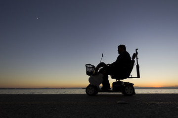 silhouette of a person with disabilities on wheelchair on the su