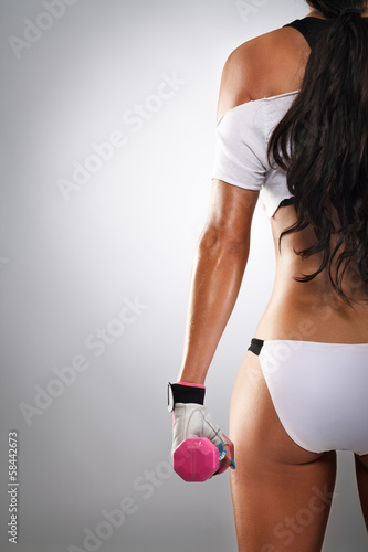 woman body from back holding dumbbells