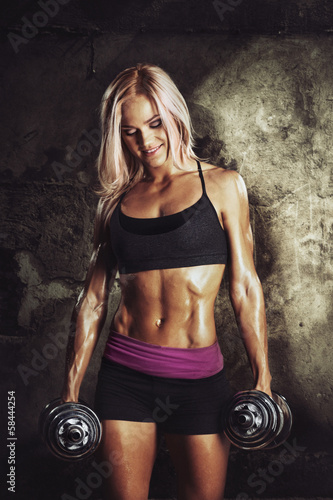 The athletic blonde with dumbbells on a grunge background