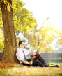 Young man with flowers sitting on grass and checking the time
