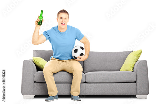 Happy cheerful male sport fan with ball and beer watching sport