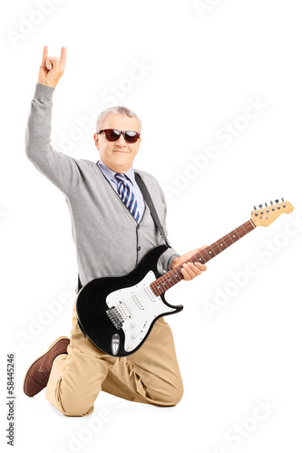 Cool senior man with an electric guitar giving a hand sign