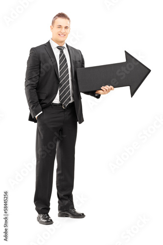 Smiling businessman in black suit holding a big arrow