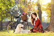 Beautiful female sitting down on a grass with her dog in a park